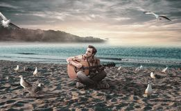 Young man playing guitar on the beach. Surrounded by seagulls Royalty Free Stock Image
