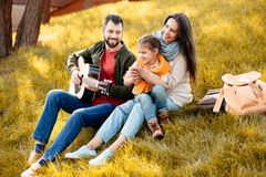 Young man playing guitar with family. Family with daughter relaxing on a grassy hill while father is playing the guitar stock photography