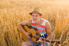 Young man playing guitar in the field on sunset Stock Photos