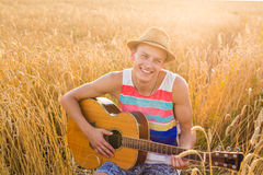 Young man playing guitar in the field on sunset Stock Image