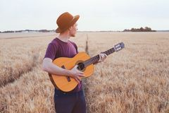 Young man playing guitar, romantic music love song. Young man playing guitar in the field at sunset, romantic love song stock image
