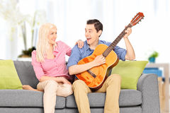 Young man playing guitar for his girlfriend at home Royalty Free Stock Photography