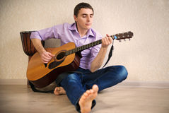 Young man playing with guitar. At home Stock Image