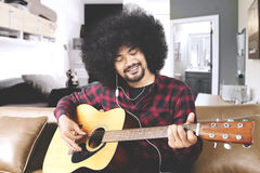 Young man playing guitar at home. Young afro man playing guitar on sofa while listening music with earphone at home Stock Photos