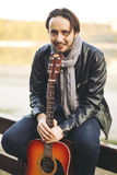 Young man playing on guitar at the lake. Portrait of young man playing on guitar at the lake Royalty Free Stock Photo
