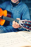 Young man playing on a guitar. Music notes. Classic instrument. Vintage colors Stock Image