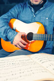 Young man playing on a guitar. Music notes. Classic string instrument. Jeans shirt. Vintage colors Royalty Free Stock Photo