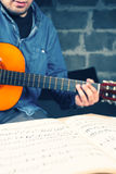 Young man playing on a guitar. Music notes. Jeans shirt. Vintage colors Stock Images