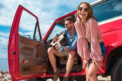 Young man playing guitar near car with cheerful girlfriend stock photography