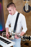 Young man playing guitar next to the keyboards Royalty Free Stock Photography