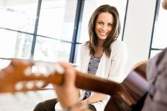 Young man playing the guitar in office. After work Royalty Free Stock Images