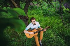 Young man playing guitar outdoor under the tree stock photos