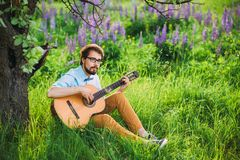 Young man playing guitar outdoor under the tree stock photography