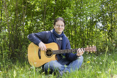 Young man playing guitar outdoors in green fields Stock Image