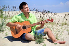 Young man playing guitar outdoors Royalty Free Stock Photos