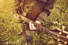 Young man playing on the guitar outdoors. Royalty Free Stock Image