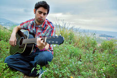 Young man playing guitar outside Stock Image