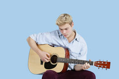 Young man playing guitar over blue background Stock Image