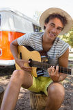 Young man playing guitar in the park. Portrait of young man playing guitar in the park Stock Photo