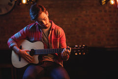 Young man playing guitar. In pub Royalty Free Stock Image