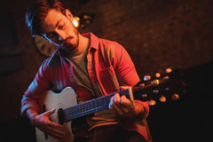 Young man playing guitar. In pub Stock Photography
