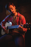 Young man playing guitar. In pub Royalty Free Stock Photo