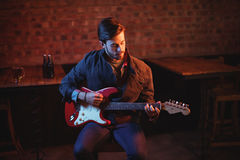 Young man playing guitar. In pub Royalty Free Stock Photos
