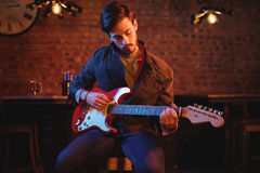 Young man playing guitar. In pub Stock Photos