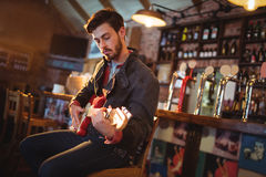 Young man playing guitar. In pub Royalty Free Stock Photography