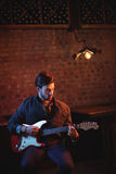 Young man playing guitar. In pub Stock Photo