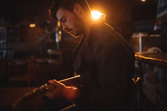 Young man playing guitar. In pub Royalty Free Stock Images