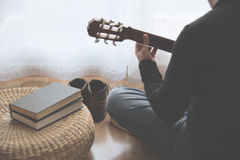 Young man playing the guitar after reading a book. Copy space for Editor`s text Stock Image
