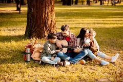 Young man playing on a guitar and relaxing on a picnic blanket. Young men playing on a guitar and relaxing on a picnic blanket with his family royalty free stock photo