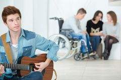 Young man playing guitar in school. Young men playing a guitar in a school Royalty Free Stock Photos