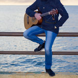 Young man playing guitar. On seaside promenade Stock Images