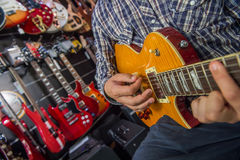 Young man playing the guitar in a shop. France Stock Photography