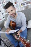 Young man playing guitar and sitting on couch. Young man playing guitar and sitting on the couch Stock Images