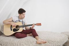 Young man playing guitar while sitting on fur sofa Royalty Free Stock Photos