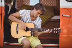 Young man playing guitar while sitting in motor home. At forest Stock Images