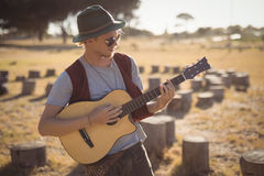 Young man playing guitar while standing on field Stock Images