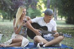 Young man playing guitar to his girl royalty free stock photos