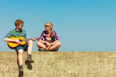 Young man playing guitar to his girlfriend outdoor Royalty Free Stock Photography