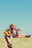 Young man playing guitar to his girlfriend outdoor Stock Photo