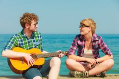 Young man playing guitar to his girlfriend by seaside Stock Photos