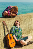 Young man playing guitar to his girlfriend by seaside Royalty Free Stock Images