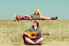 Young man playing guitar to his girlfriend by seaside. Young men playing guitar to his girlfriend outdoor by seaside - dating couple royalty free stock photography