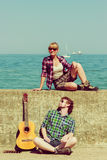 Young man playing guitar to his girlfriend by seaside Stock Images