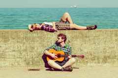 Young man playing guitar to his girlfriend by seaside. Young men playing guitar to his girlfriend outdoor by seaside - dating couple Royalty Free Stock Photo