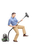 Young man playing guitar on a vacuum cleaner Royalty Free Stock Images