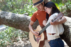 Young man playing guitar for woman in trees Stock Image